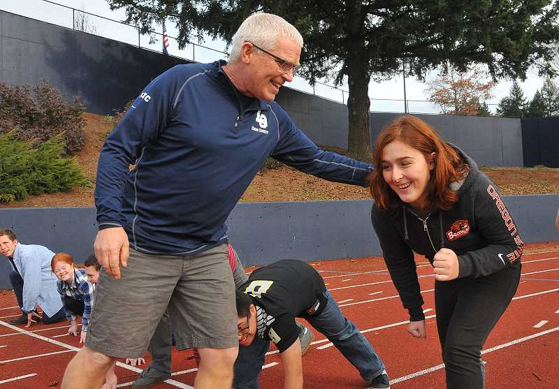 Photo Credit: REVIEW, TIDINGS PHOTO: VERN UYETAKE - Emily Rich gets some encouragement from Eric Lider at track practice at Lake Oswego High School. Despite retiring as LOHS head track coach, Lider is still making a difference in the lives of students.