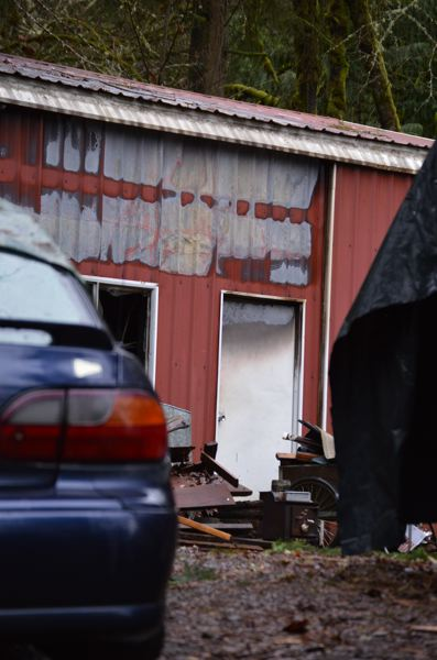 Photo Credit: COURTNEY VAUGHN - Broken windows are left on a large shed in Scappoose in the wake of a fire that burned the building Friday, Feb. 6. Two men who were staying in the building were  helped by the American Red Cross.