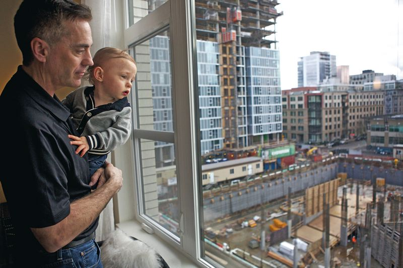 Photo Credit: TRIBUNE PHOTO: JAIME VALDEZ - Portland real estate developer Bob Ball, and his son Parker, look from the model unit of the Parker apartment building in the Pearl District. The window looks down on the site of the Overton Apartments, which will block his view but have to play catch up when it comes to finding renters.