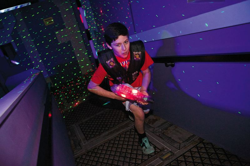 Photo Credit: JAIME VALDEZ - Jake LeBrun, 12, a seventh grader at St. Cecilia School, pursues the other team in a laser tag game at SuperPlay.