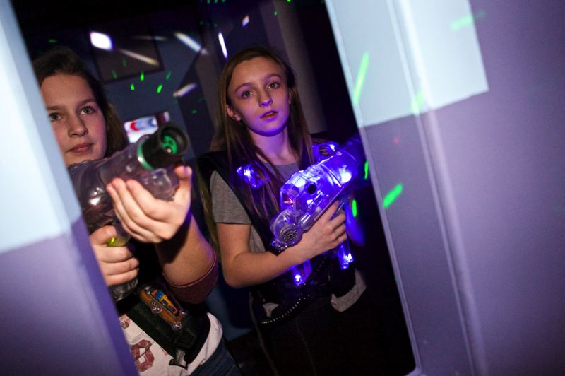 Photo Credit: JAIME VALDEZ - Hayley Schuler, 13, left, and Haley Gentry, 12, both seventh graders at St. Cecilia School, pursue the other team in a laser tag game at SuperPlay.