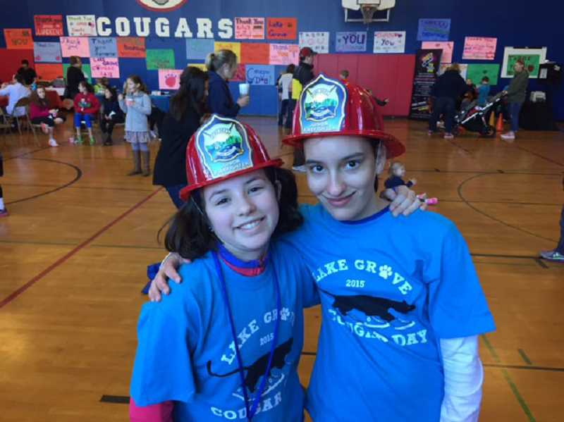 Photo Credit: SUBMITTED PHOTO - Lake Grove fifth-graders Tiffany Brynn (left) and Kaelyn Nimmoor enjoy Cougar Day activities, including a visit from the Lake Oswego Fire Department.