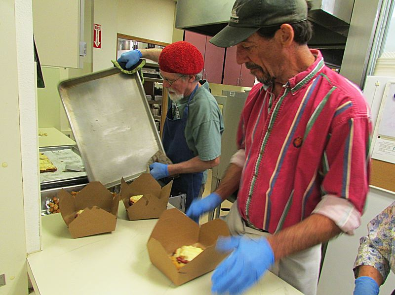 DARRYL SWAN - Scappoose Senior Center chef Scott Kreitman (left) and employee Craig McKay package Reuben sandwiches and tater tots as part of the center's Meals on Wheels program. Kreitman said the center, on a busy day, prepares up to 70 meals.