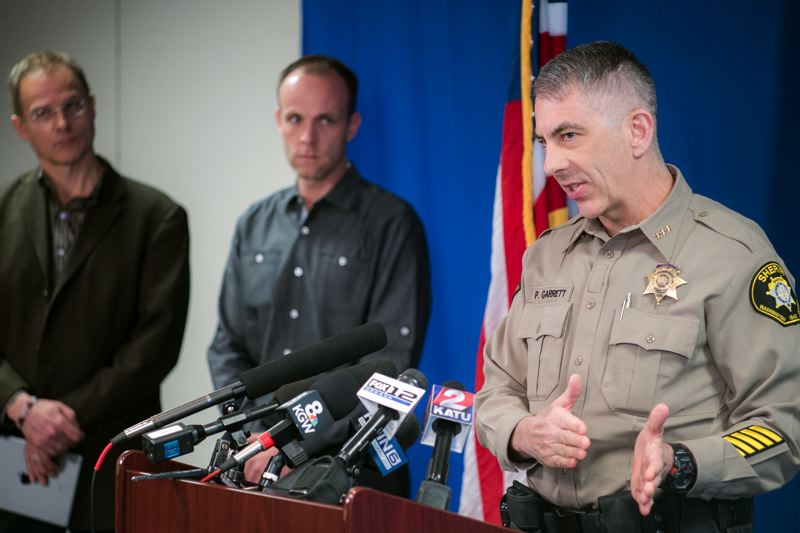 CHASE ALLGOOD - Rich Jones (far left) and Chris Laube (center) listen to Washington County Sheriff Pat Garrett talk about the arrest of Jaime Tinoco for the August 2014 murder of their daughter and wife, Nicole Laube, at a Wednesday afternoon press conference in Hillsboro.