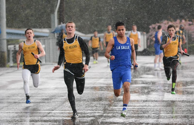JOHN WILLIAM HOWARD - Braving the downpour, St. Helens' Bryce Bumgardner and La Salle's Parker Cardwell run neck-and-neck during the final leg of the 4x100 meter relay on Wednesday afternoon.