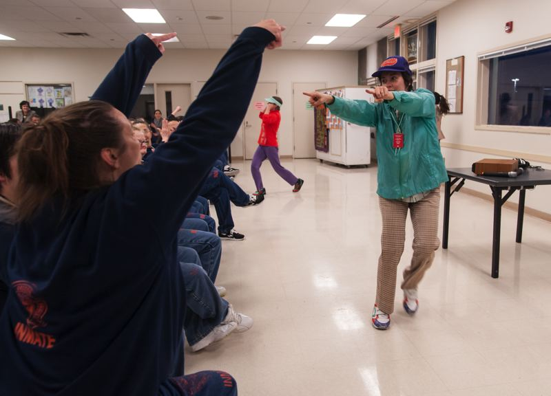 SPOKESMAN PHOTO: JOSH KULLA - Hand2Mouth cast member Maesie Speer gets motivated with Coffee Creek Correctional Facility inmates during the theater groups recent performance at the Wilsonville prison.