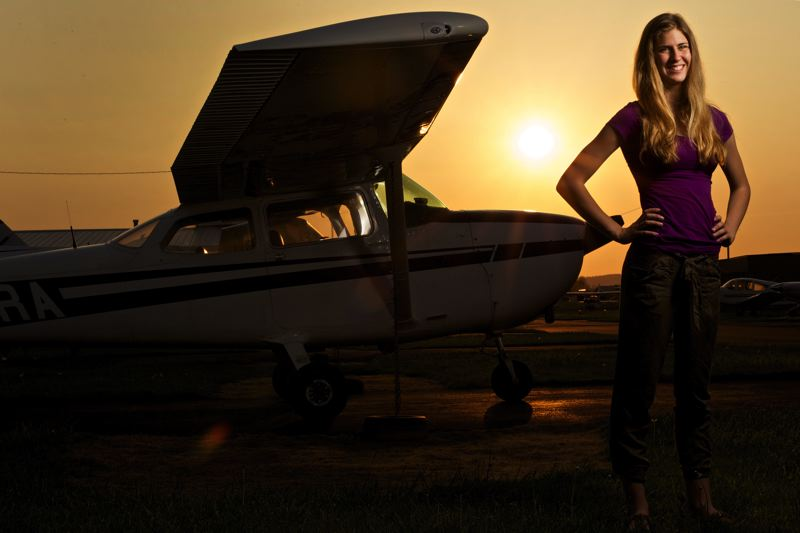 TIMES PHOTO: JAIME VALDEZ - Ellie Parker, a junior at Tualatin High School, flies Cessna airplanes similar to the one behind her at the Aurora St,ate Airport.