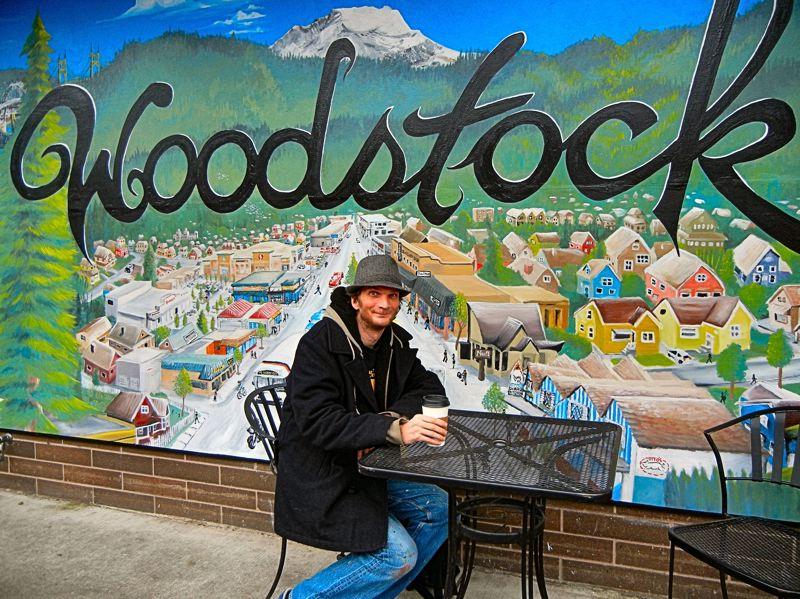 ELIZABETH USSHER GROFF - Musician and muralist Michael Burge Smith, here shown seated, has created another mural for the Woodstock neighborhood; it appears on the west outside wall of Papaccinos Coffee Shop on S.E. 44th at Woodstock Boulevard.