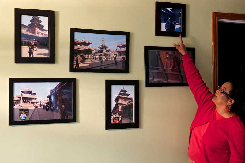 TIMES PHOTO: JAIME VALDEZ - Ganga Sharma, president of the Nepali Association of Oregon, shows pictures from Nepal. All of the buildings in these photos were destroyed by last weeks earthquake, she said.