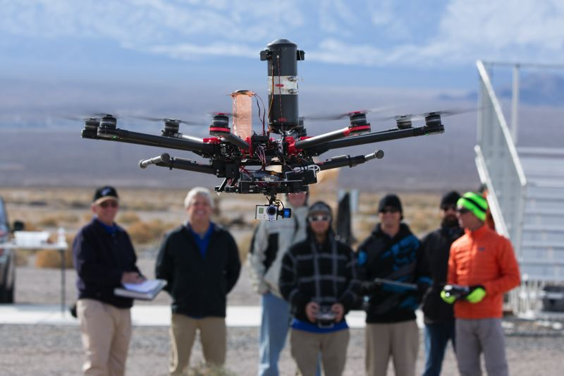 COURTESY JONATHAN NATIUK FOR SKYWARD - Staff from Skywards flight ops team test a custom built DJI S1000 at the Nevada Test and Training Range in February 2015. The vertical, black cyclinder is a parachute.