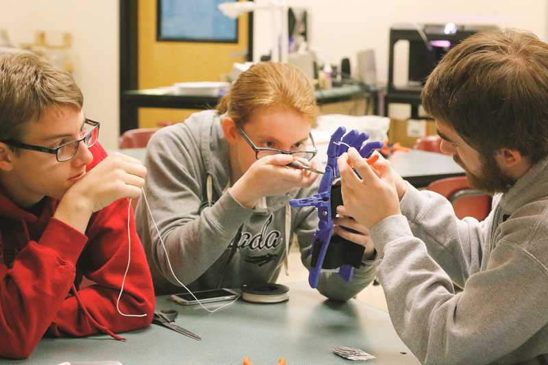 TIMES PHOTO: JONATHAN HOUSE - Victoria Brager, center, does some fine-tuning on a prosthetic hand she and fellow engineering students in Jacob Small's class printed at Southridge High School.