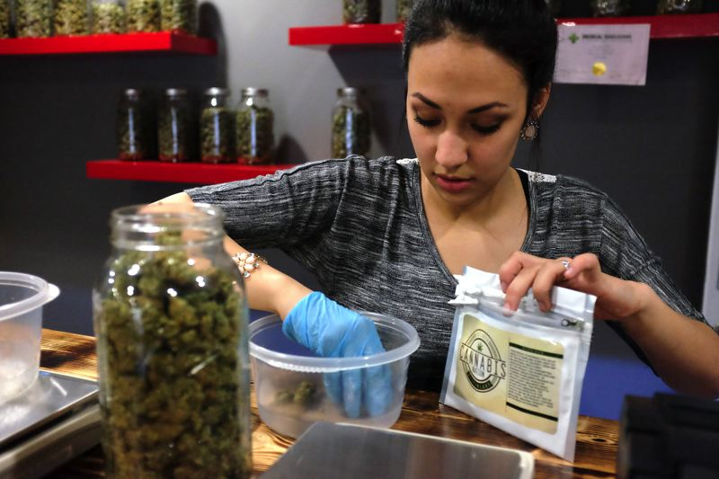 TIMES PHOTO: JAIME VALDEZ - Shaina Lewis, a budtender, carefully measures product at Blooming Deals.