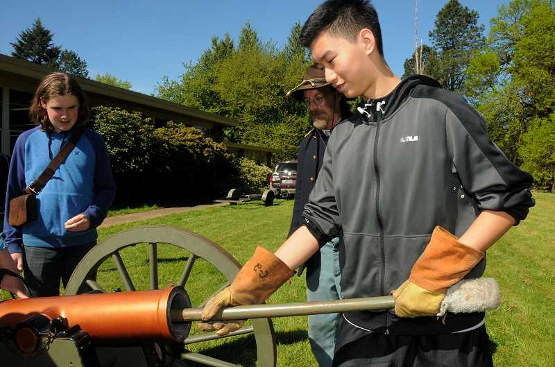 REVIEW PHOTO: VERN UYETAKE - Max Franz helps prepare the cannon for firing
