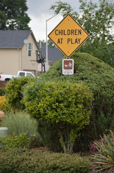 SPOTLIGHT PHOTO: MARK MILLER - A 'Children At Play' sign stands at the corner of Fifth and Pacific streets in Columbia City. Several portable basketball hoops are positioned on or along Fifth Street, as well as other neighborhood streets like Park Drive and Tahoma Street.