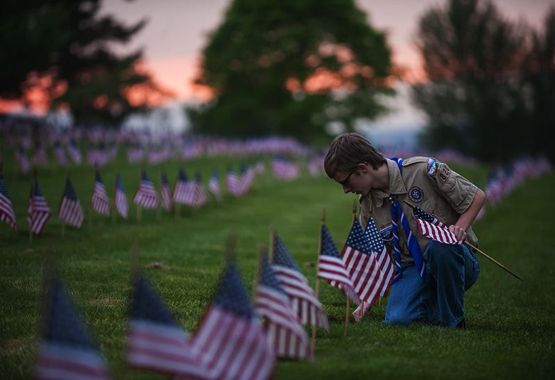 OUTLOOK PHOTO: JOSH KULLA - Gresham Boy Scout Alonzo Perry of Troop 820 places an American flag at Willamette National Cemetery.