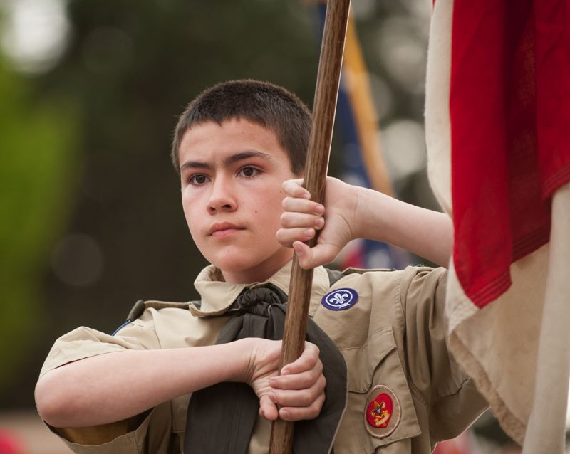 OUTLOOK PHOTO: JOSH KULLA - A Scout concentrates Thursday while carrying his Troop's colors at Willamette National Cemetery.
