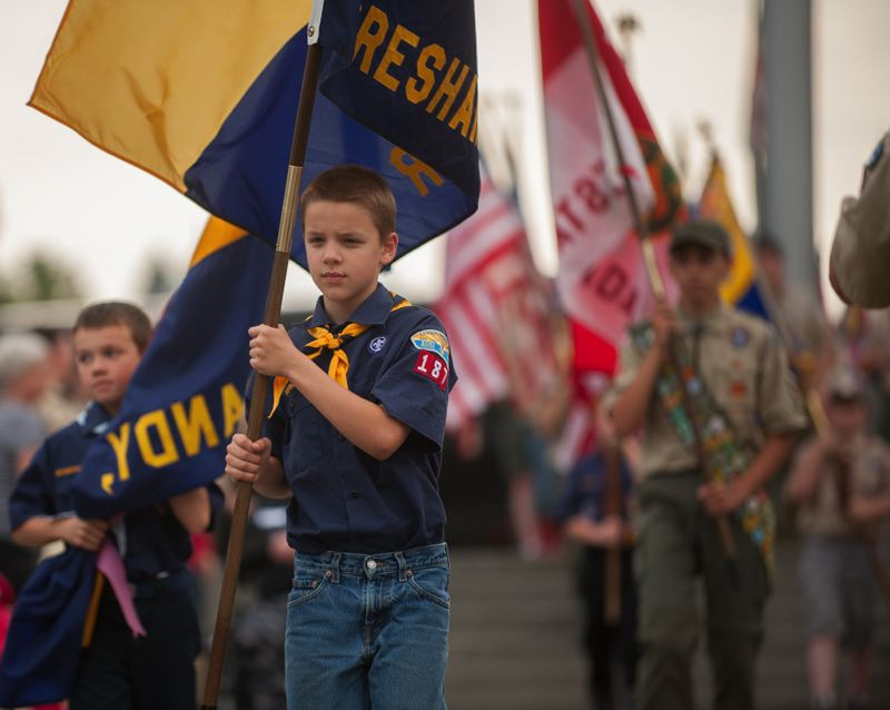 OUTLOOK PHOTO: JOSH KULLA -  A Cub Scout carries his Pack's colors Thursday at Willamette National Cemetery.