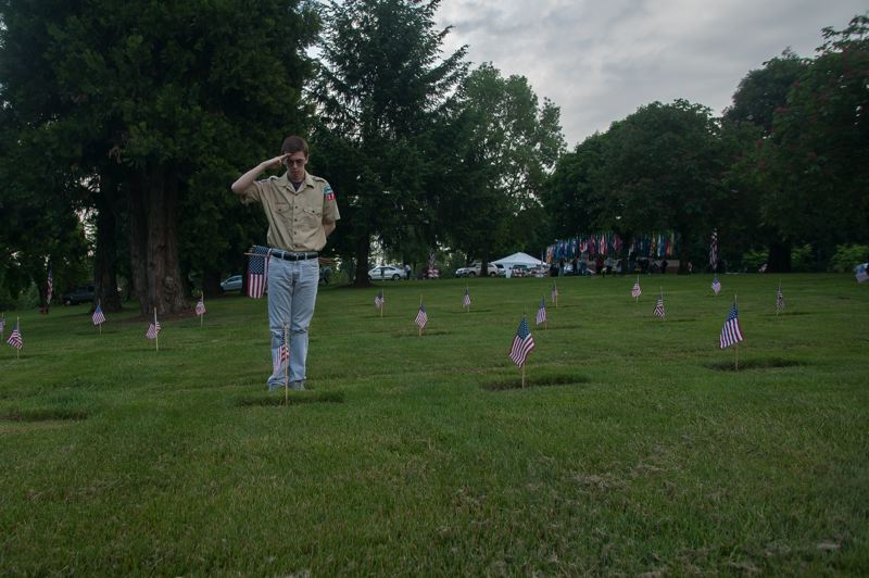 OUTLOOK PHOTO: JOSH KULLA - Gresham Boy Scout Spencer Livermore salutes the grave of a veteran at Willamette National Cemetery.