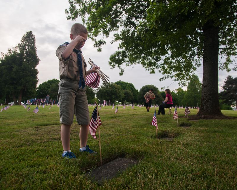 OUTLOOK PHOTO: JOSH KULLA - Troop 171 Boy Scout Spence Cheney salutes the grave site of a veteran.