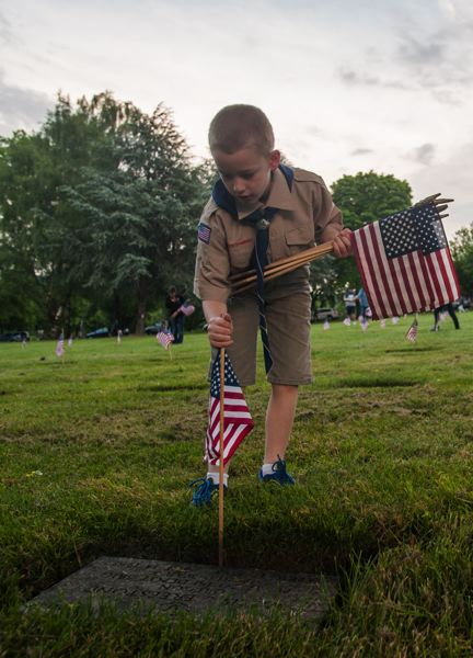 OUTLOOK PHOTO: JOSH KULLA - Troop 171 Boy Scout Spence Cheney places a flag at a Willamette National Cemetery grave site.