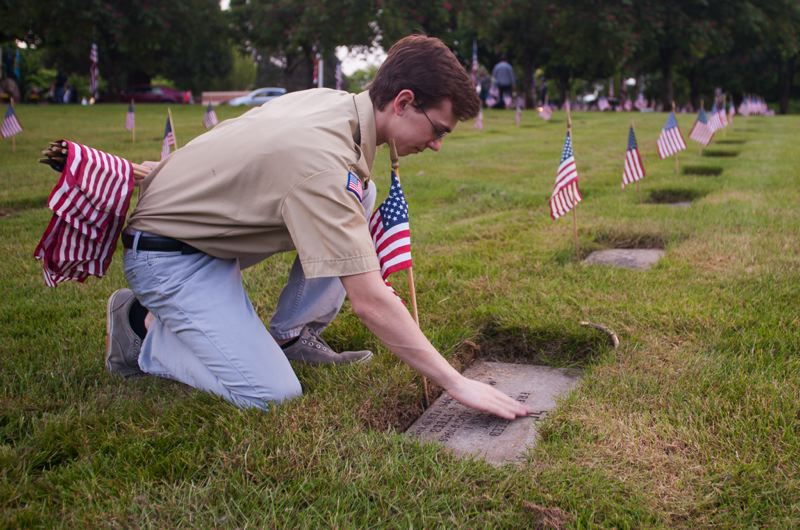 OUTLOOK PHOTO: JOSH KULLA - Troop 171 Boy Scout Spencer Livermore cleans a headstone after placing an American flag at Willamette National Cemetery.