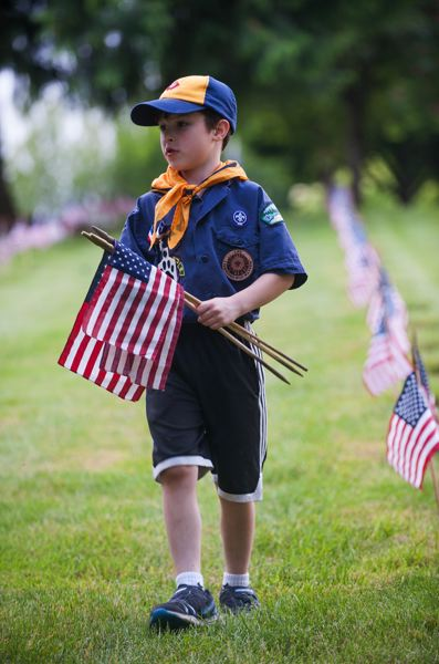 OUTLOOK PHOTO: JOSH KULLA - Damascus Cub Scout Carson Ryder places flags at Willamette National Cemetery.