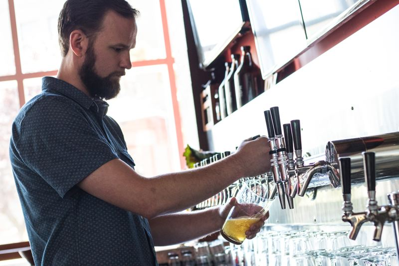 TRIBUNE PHOTO: JONATHAN HOUSE - Sean Hiatt pours a beer at the Civic Taproom.