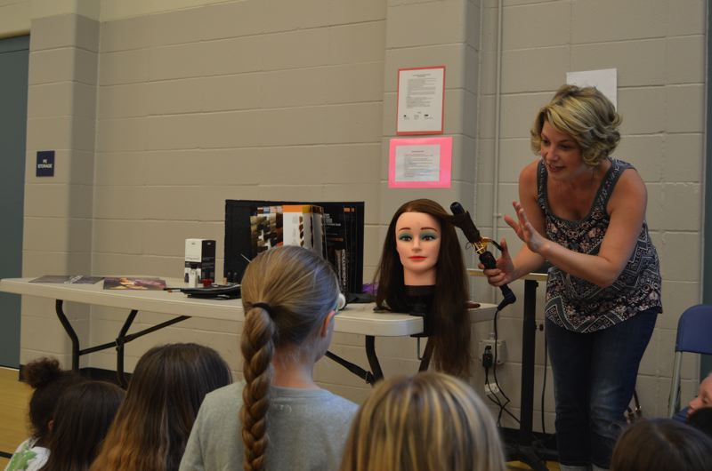 SPOTLIGHT PHOTO: MARK MILLER - Summer Weitman teaches students at Grant Watts Elementary School about hairdressing during a career expo Monday, June 8.