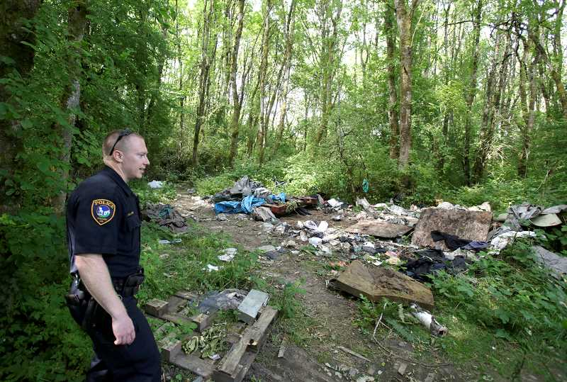 TIMES PHOTO: JONATHAN HOUSE - Tigard Police Officer Jason Tillotson walks toward a homeless camp on Southwest Dartmouth Street, Tuesday morning. The city has a large homeless population, but a group of local churches is hoping to open a day center in the near future.