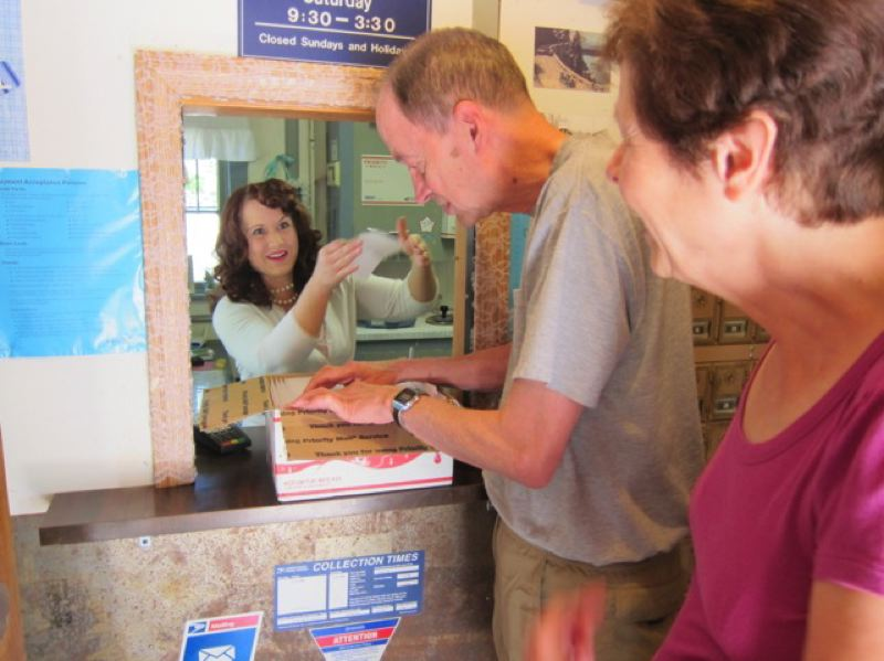 CONTRIBUTED PHOTO: QUINTON SMITH - Bridal Veil Postmaster Tara Stiller helps Frank and Lona Arnold with invitations for their daughters Aug. 14 wedding. The Arnolds used to live in nearby Latourell so knew where to go to get special postmarks for their invitations.