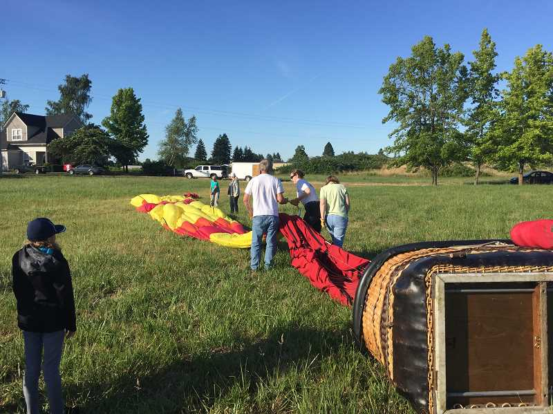 TIMES PHOTO: GEOFF PURSINGER - Landed! After touching down in a large open area in Woodburn, Smith's crew works to disassemble the balloon for the long ride back to Tigard.