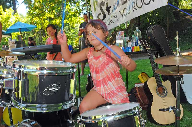REVIEW PHOTOS: VERN UYETAKE - Six-year-old Natalie McCormick of Lake Oswego enjoys learning to play drums at the RMC Studios booth, one of the Kids Get Creative activities on Friday.