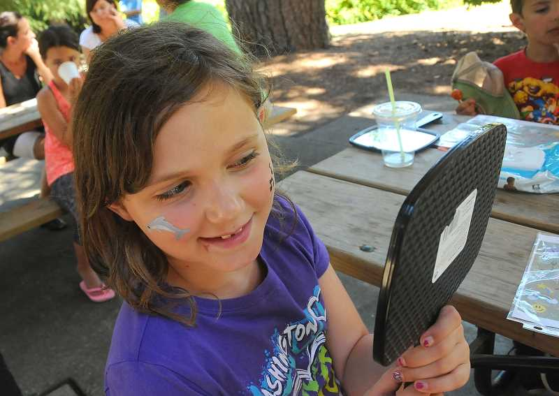 REVIEW PHOTOS: VERN UYETAKE - Eight-year-old Payton Walker of Lake Oswego admires her painted face, the handiwork of Lake Osego High student Cher Fong.