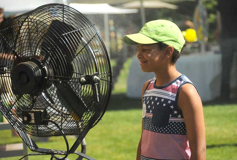 REVIEW PHOTOS: VERN UYETAKE - David Miller, 10, of Lake Oswego finds the perfect spot to cool off at the Festival of the Arts on Friday afternoon.