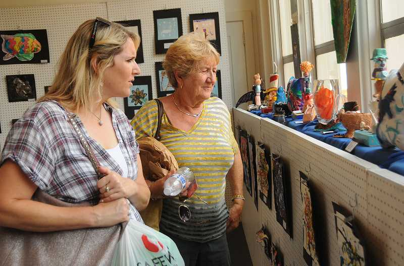 REVIEW PHOTOS: VERN UYETAKE - Laurie (left) and Erna Treske of West Linn admire the work of student artists at the Lakewood Center.  8: Audrey Underdahl of Lake Oswego shops for the perfect hat at Art in the Park.
