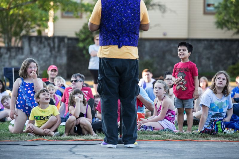 TIMES PHOTO: JONATHAN HOUSE - Children look on as entertainer Angel Ocasio performs a trick during a performance at the Lake of the Commons Tuesday night.