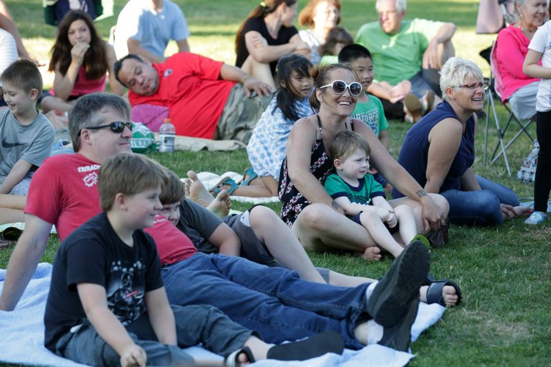 TIMES PHOTO: JONATHAN HOUSE - Families sit and enjoy a performance by children's entertainer Angel Ocasio at the Lake of the Commons on Tuesday.