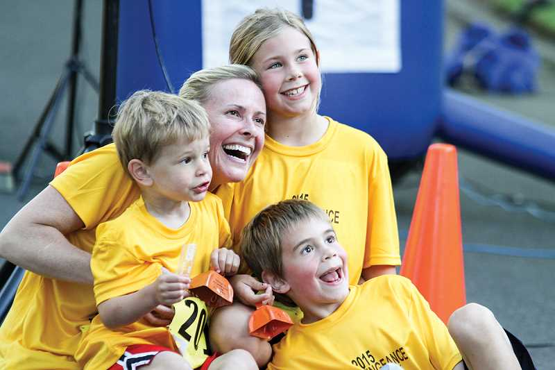 NEWS-TIMES PHOTO: AMANDA MILES - Jenna Jacobson, of Hingham, Mass., poses with daughter Brady, 8, and sons Sawyer, 6, and Dylan, 3, at the conclusion of last Thursday's Viking Vengeance road race in Forest Grove.