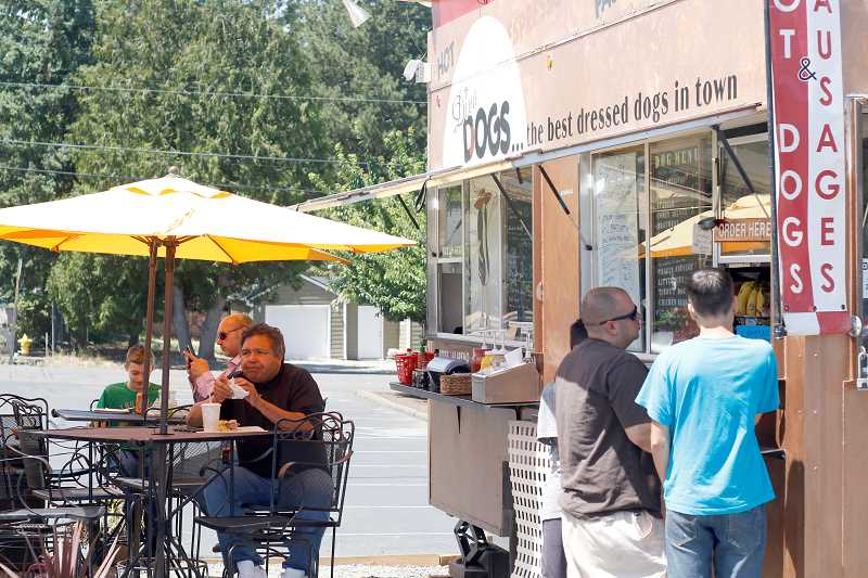 TIMES PHOTO: JONATHAN HOUSE - Diners belly up for a bite at Cafe Diva Dogs and a half dozen other mobile restaurants at The Eating Place at Aloha Mall. Beaverton soon will allow similar food cart pods.
