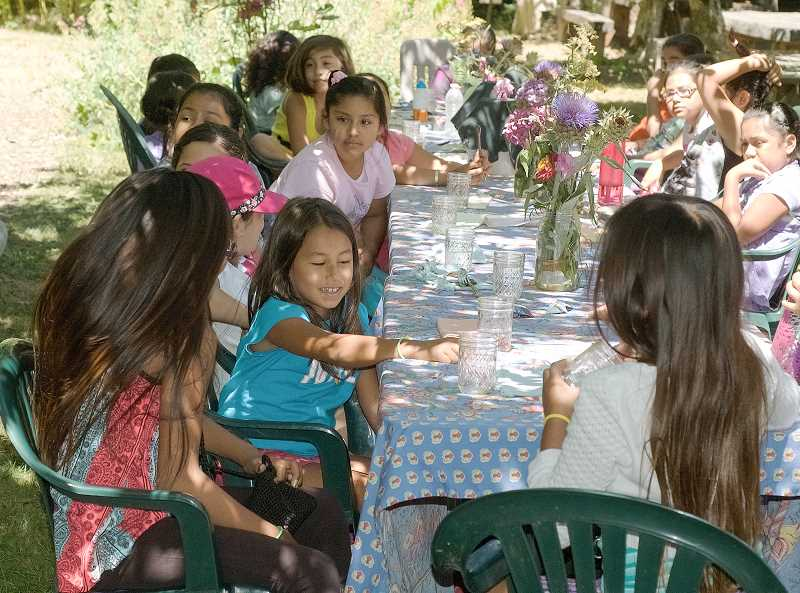 Adelante Chicas campers sit down to enjoy food they harvested and prepared themselves at Nana Cardoon farm.