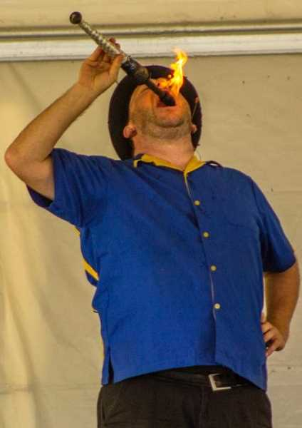 NEWS-TIMES PHOTO: TRAVIS LOOSE - Undeterred by the 100-plus degree temperatures Thursday afternoon, Greg Frisbee casually swallowed fire during his Rubber Chicken Show at the Washington County Fair. Asked by a child in the audience why he eats fire, 'Because people like it' was Frisbee's cool response.
