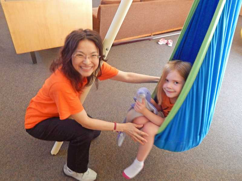 REVIEW PHOTO: CLIFF NEWELL - Yu-Wen Huang was happy to be on the Orange Team for the Creative Arts Summer Camp at Marylhurst University. Helping Yu-Wen have fun is 6-year-old camper Madeline Decker.