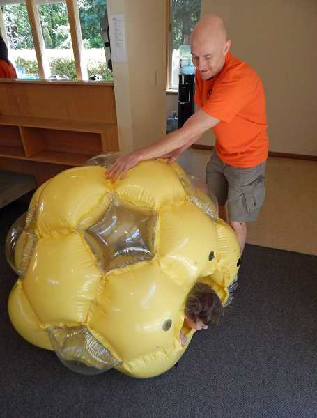 REVIEW PHOTO: CLIFF NEWELL - Chris Koroshetz, a counselor at the Creative Arts Summer Camp at Marylhurst University, has fun rolling a camper in a giant plastic inflated ball on the camp's final day.
