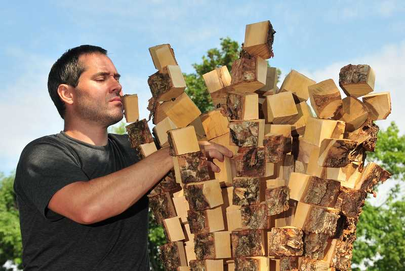 REVIEW PHOTOS: VERN UYETAKE - New York artist Anthony Heinz May crafted his wood sculpture onsite for Lake Oswegos Gallery Without Walls. The piece is one of 14 that will be officially unveiled on Sunday.