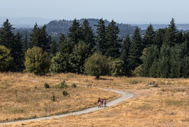 TRIBUNE PHOTO: JONATHAN HOUSE - A family hikes along a mixed-use trail for pedestrians, horses and bikes at Powell Butte Nature Park.