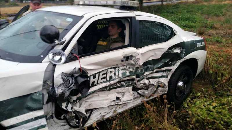 SUBMITTED PHOTO - Clackamas County Deputy Sheriff Garrett Grimm waits for help after his patrol car was struck early Sunday on Highway 212 in Damascus.