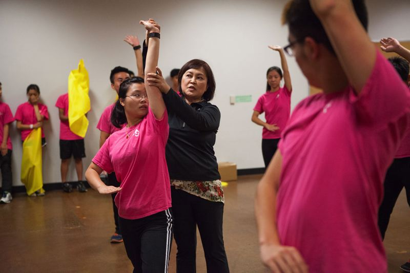 TIMES PHOTO: ADAM WICKHAM - Ming Chang, a dance instructor, shows a student how to finish a movement as members of the Formosa Association of Student Cultural Ambassadors prepare for a performance at Saturdays Beaverton Night Market.
