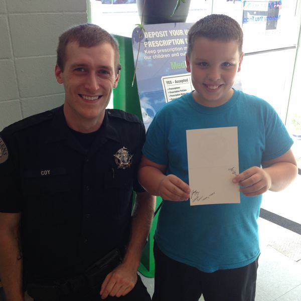 PHOTO COURTESY OF THE ST. HELENS POLICE DEPARTMENT - Officer Jamin Coy smiles with a boy who picked up an autograph card Wednesday, Sept. 10. The autograph contest runs through Sept. 18.