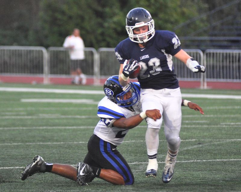 MATTHEW SHERMAN - Lake Oswego tailback Max Mattern tries to shake a South Medford tackle during the Lakers' 31-26 victory Friday.