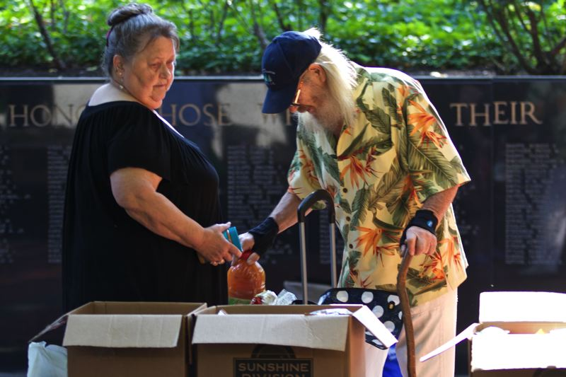 TRIBUNE PHOTO: JAIME VALDEZ - Rosetta Stone of Portland helps her best friend, Gary Jennings of Mill City, pack a box of food after last weeks Portland Veterans Stand Down event. Stone worked on a United Service Organizations Inc. project on a U.S. naval base; Jennings is a Navy Vietnam War veteran.
